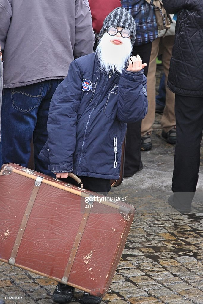 A child wearing a fake beard and glasses holds a suitcase as people gather on Masaryk Square in Zabreh, central Moravia, Czech Republic, on February 17, 2013, for an attempt to bring a record number of suitcases to one place. 579 people with suitcases came to the place to honor Czech adventurer, traveller and gold digger Jan Eskymo Welzl. The record will be officially registered in the Guinness Book of Records.