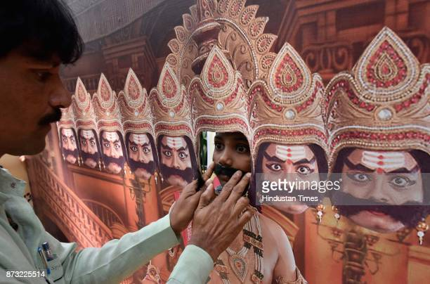 A child wearing a moustache while posing with the cutout of Ravana during Makkala Hanna Children Festival at Cubbon Park on November 12 2017 in...