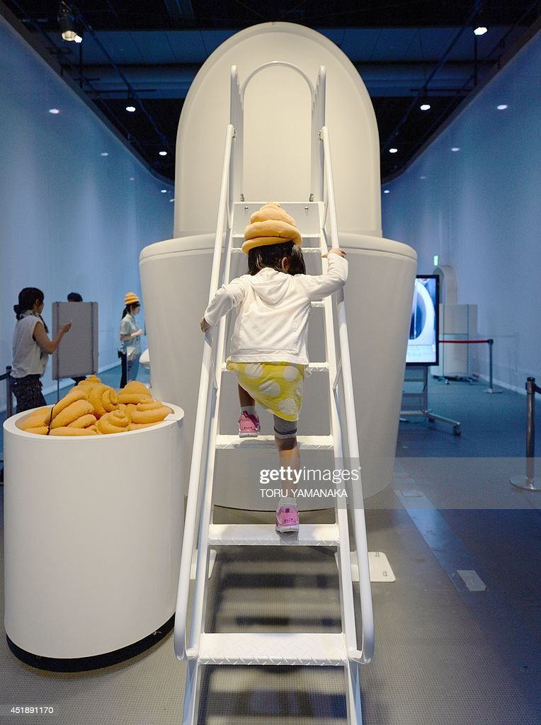 A child wearing a poo-shaped hat walks up stairs to climb on a giant toilet slide at a toilet exhibition at the National Museum of Emerging Science and Innovation in Tokyo on July 9, 2014. The exhibition, which aims at educating visitors about sewage, health and waste, will last until October 5. AFP PHOTO/Toru YAMANAKA
