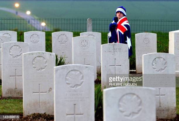 A child wearing an Australian flag walks past graves at the Australian War Memorial in the northern French city of VillersBretonneux on April 25 2012...