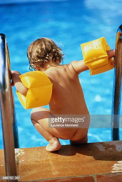 Child (1-3) wearing arm bands climbing into swimming pool