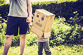 Child wearing box with robot face on it