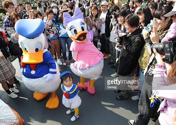 A child wearing Donald Duck is welcomed by Donald Duck and Daisy Duck at reopened Tokyo Disneyland on April 15 2011 in Urayasu Chiba Japan The theme...