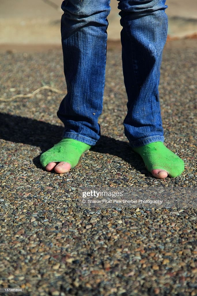 Child wearing green socks with holes : Stock Photo