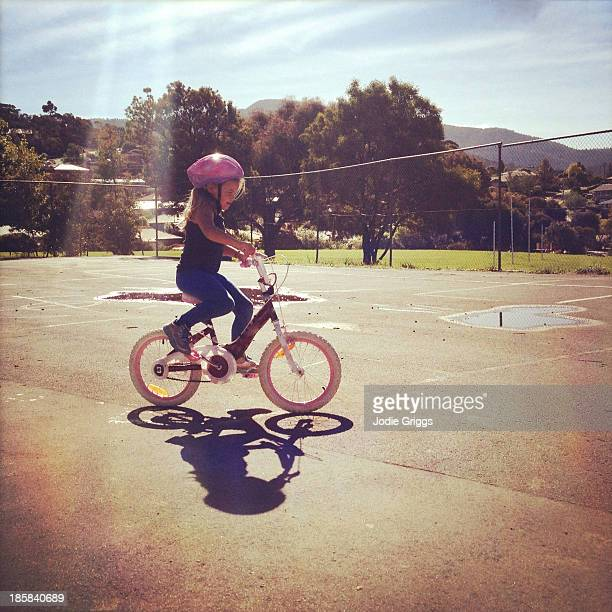 Child wearing helmet riding a bike on summer day