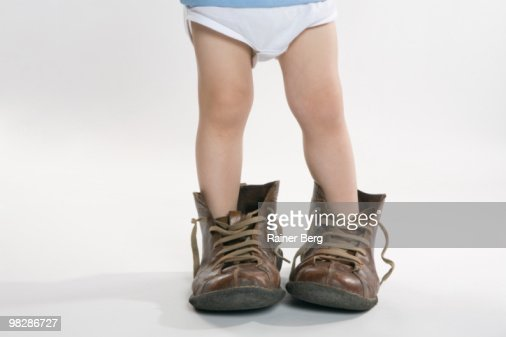 Child wearing oversized shoes, low section