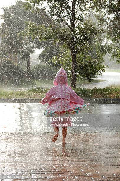 Child wearing raincoat and running
