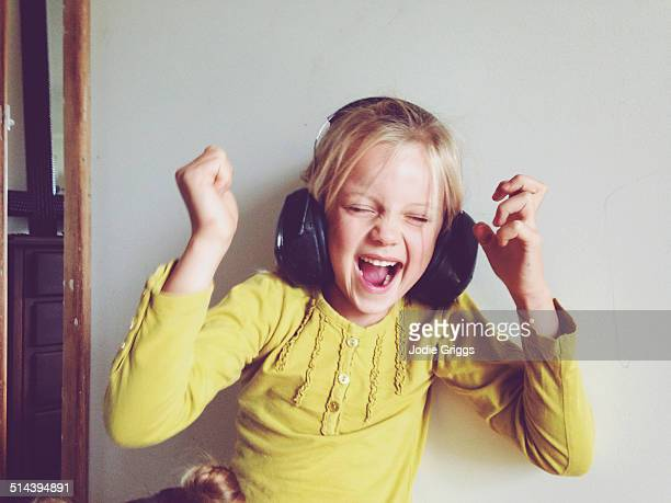 Child wearing safety earmuffs screaming loudly