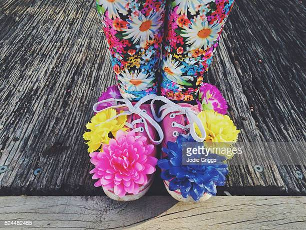 Child wearing shoes covered in colourful flowers