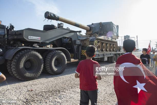 A child wearing Turkish flag looks on as Turkish Army's armoured vehicles are deployed to the Reyhanli border due to the transition to Idlib...