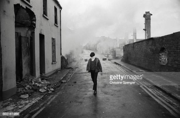 A child wears a mask to protect his nose and mouth as he makes his way down a deserted laneway in Londonderry contaminated by gas