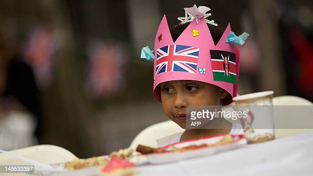 A child wears a paper crown with the Union Flag and the Kenyan flag on it as she joins refugees living in Britain take tea and cake at a Diamond...
