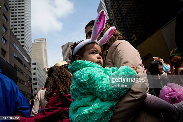 A child wears rabbit ears during the Easter Parade and Bonnet Festival along 5th Avenue March 27 2016 in New York City The parade is a New York...