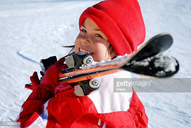 Child whith skis on shoulder