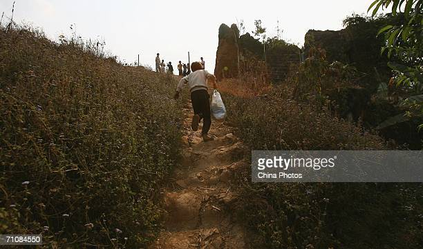 A child who helps Chinese to steal across the Myanmar and China's border carries a bag for a stowaway on March 23 2006 in Kokang Special Region of...