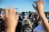 A child who was being held by her mother who was protesting the shooting death of teenager Michael Brown holds up her hands after police ordered them...
