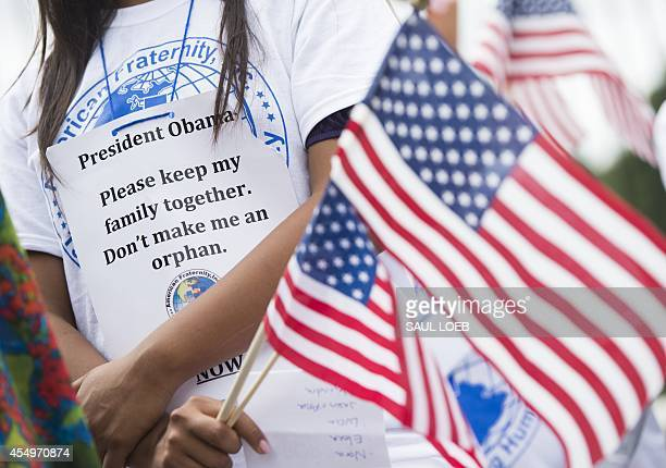 A child whose father was deported holds US flags during a protest in response to US President Barack Obama's delay on immigration reform in front of...