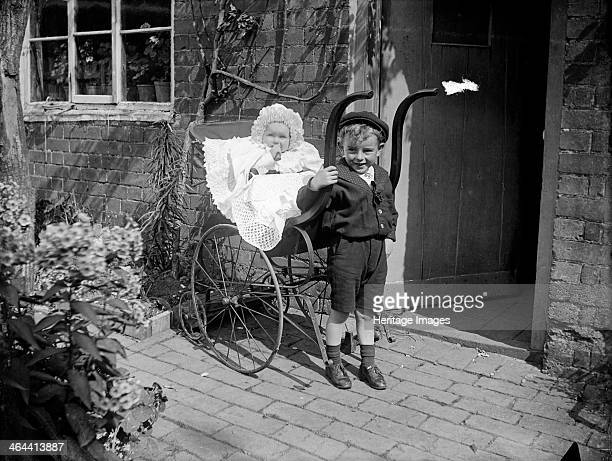 Child with a baby in a pram Hellidon Northamptonshire 1900 Franklin's young children pose outside a doorway at Hellidon Northamptonshire The baby is...