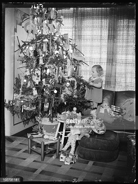 Child with a Christmas tree 1936 Traditional toys such as dolls a spinning top and wooden building blocks decorate the tree