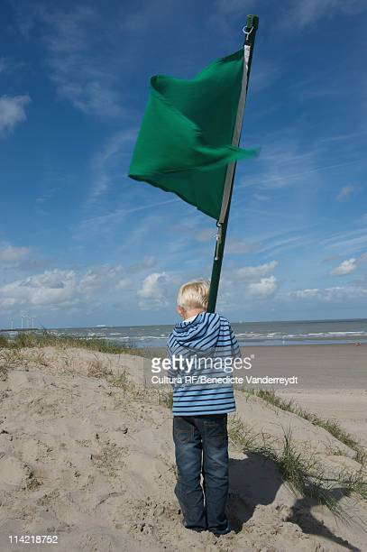 Child  with a green flag facing the sea