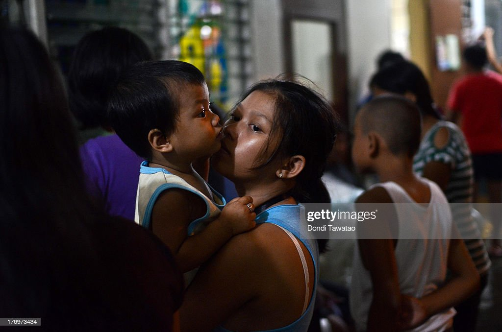 <A child with a guardian stand in line to receive medical care in a elementary school-turned evacuation center in Marikina on August 20, 2013 in Marikina City, west of Manila, Philippines. Schools, government offices and financial markets suspended classes and work except for rescues and disaster response as torrential rains enhanced by the southwestern monsoon inundated much of the metropolis for a second day. Major roads were impassable as floodwaters reached waist or neck deep in some areas forcing thousands of residents living near waterways and creeks to evacuate their homes and seek shelter. At least seven fatalities were recorded with thousands more still needing to be rescued.