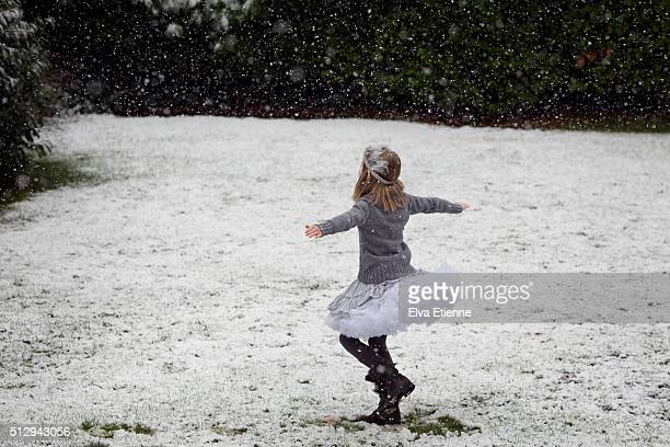 Child with arms outstretched, spinning in snow