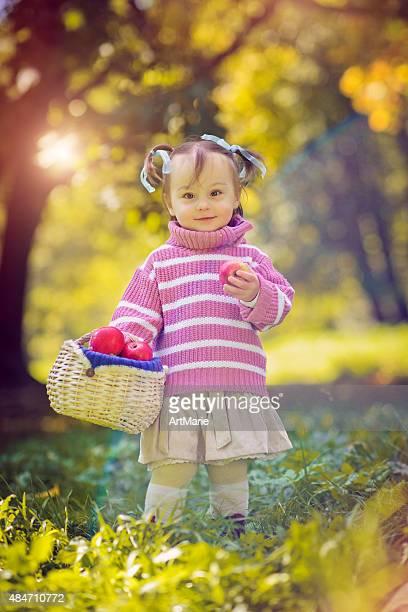 Enfant avec panier rempli de pommes