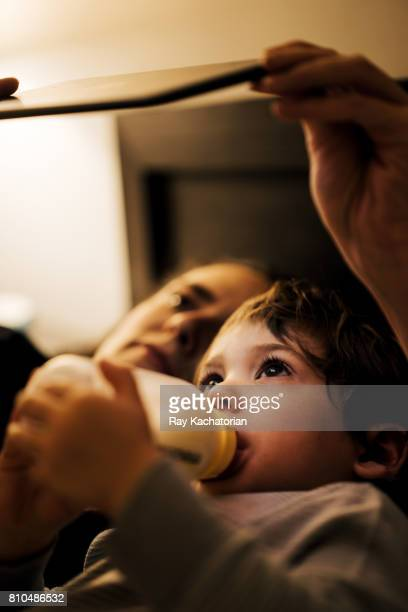Child with bottle watching mobile device with mother