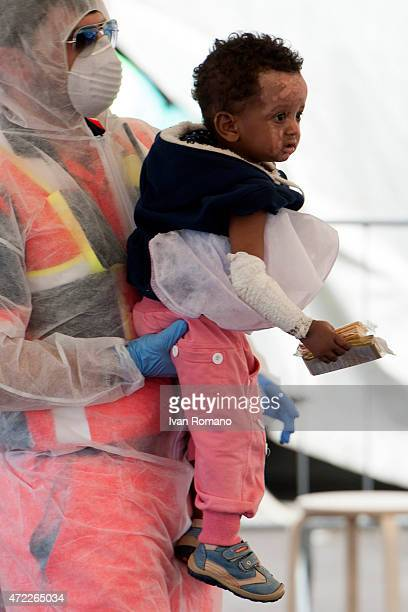 A child with burns on his face is helped by doctors after disembarking from military ship 'Bettica' following a rescue operation at sea on May 5 2015...