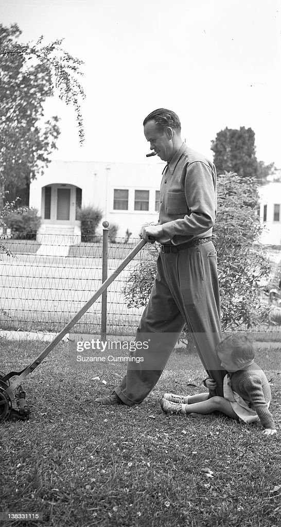 Child with dad mowing lawn : Stock Photo