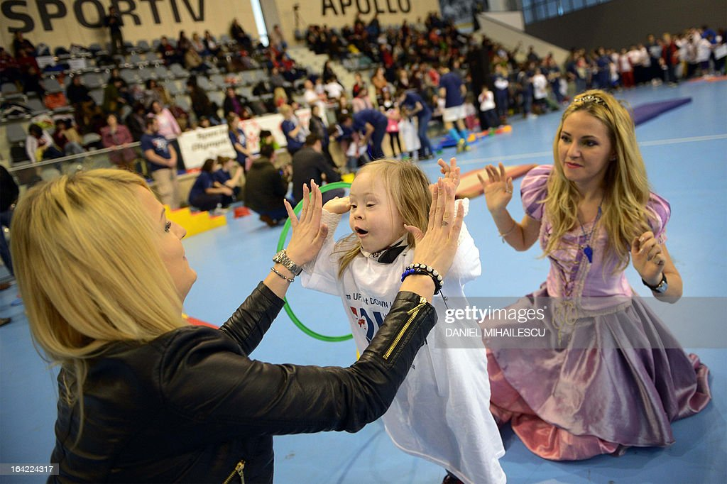 A child with Down Syndrome (C) claps hands with her mother (L) during an event marking the International Day of Down Syndrome in Bucharest March 21, 2013. March 21 aims to raise awareness among the population regarding people with Down syndrome and combat some wrong social perceptions, depriving these people of their right to an active life. AFP PHOTO / DANIEL MIHAILESCU