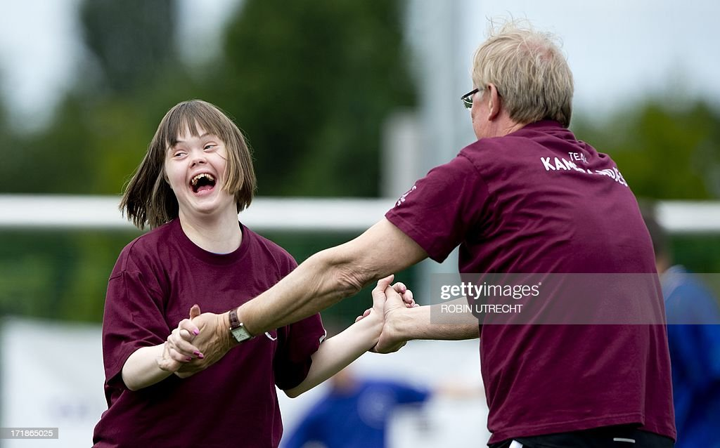 A child with Down syndrome shares a laugh with Netherlands' tv presenter Jack Spijkerman as they take part in the 'Give Down the Future' football tournament in De Toekomst stadium in Amsterdam on june 29, 2013. The tournament is organized for children and young adults with Down syndrome and hosts celebrities and former professional athletes.