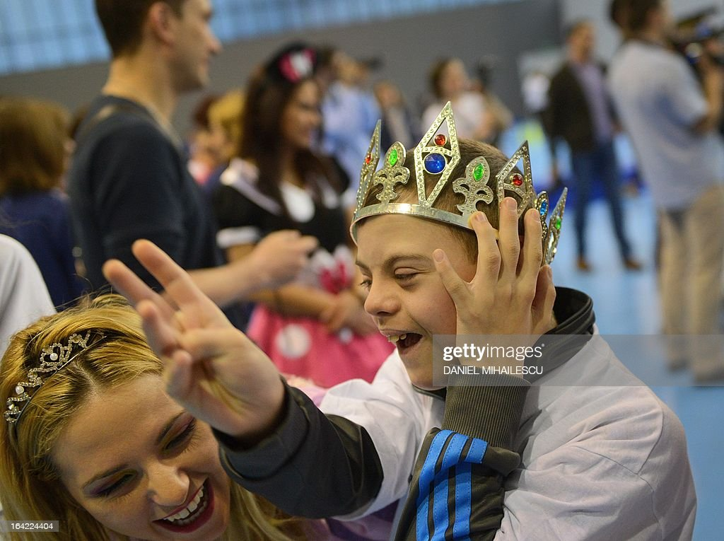A child with Down Syndrome (R) wearing a crown is pictured during an event marking the International Day of Down Syndrome in Bucharest March 21, 2013. March 21 aims to raise awareness among the population regarding people with Down syndrome and combat some wrong social perceptions, depriving these people of their right to an active life.