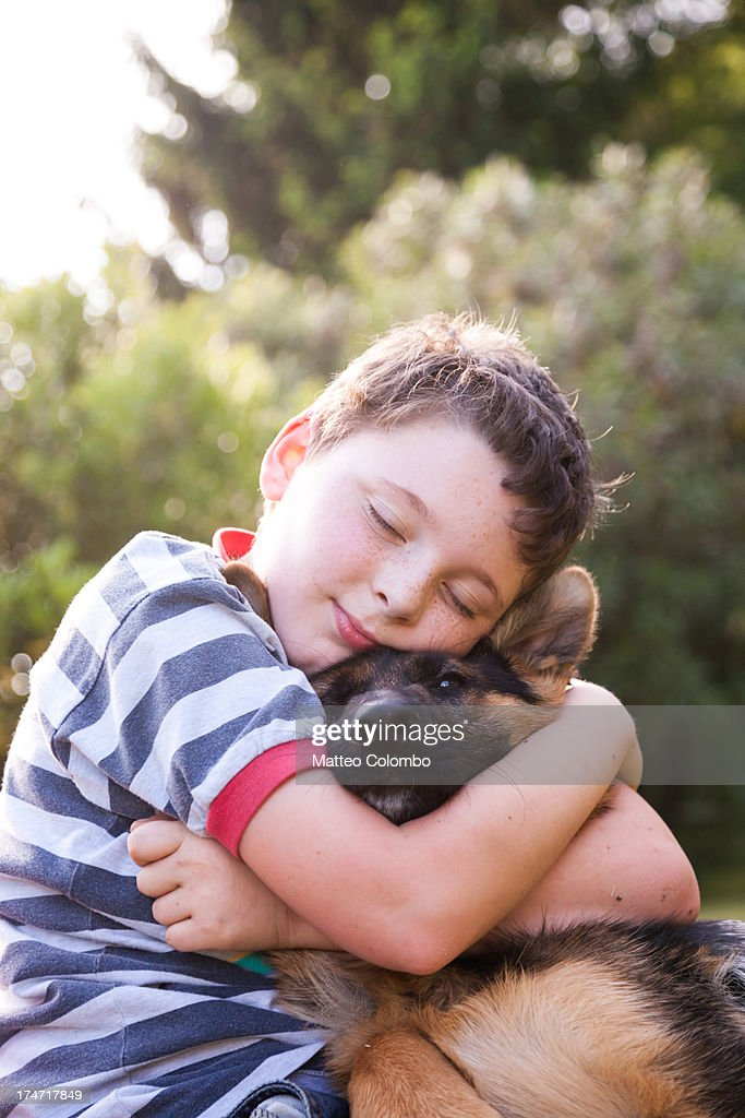Child with eyes closed embracing his pet dog : Stock Photo