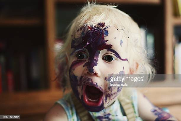 child with face covered in paint