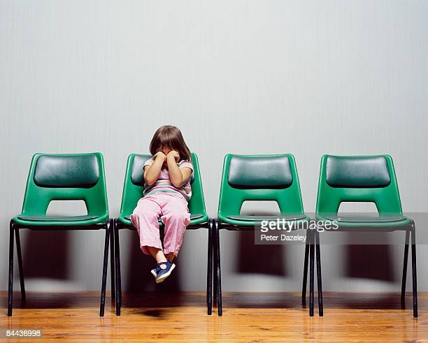 Child with hands covering eyes sitting on chair