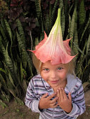 Child with large pink flower on head like a hat