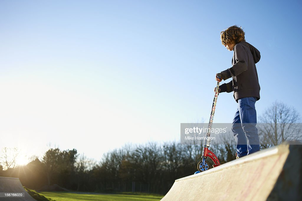 Child with micro scooter on ramp at skate park. : Stock Photo