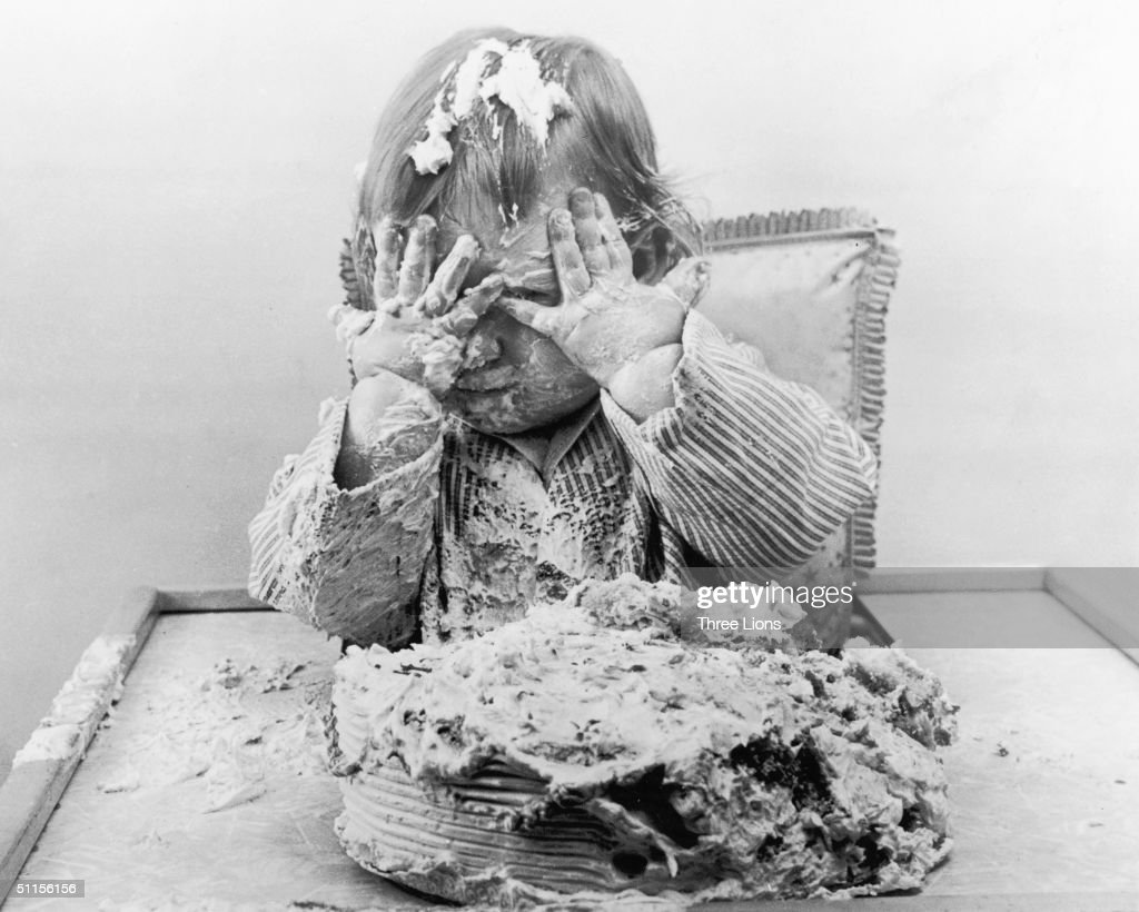 A child with more cake and icing in her hair than in her tummy, circa 1971.
