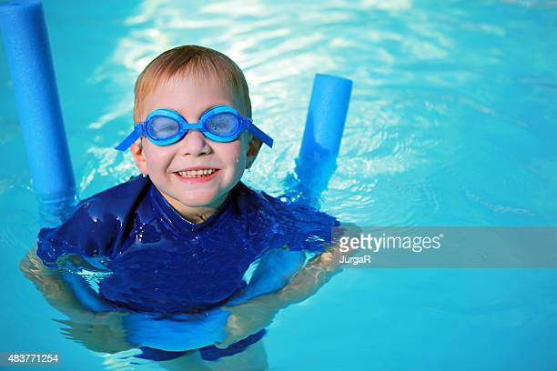 Child with Noodle Float and Swimming Goggles Learning to Swim