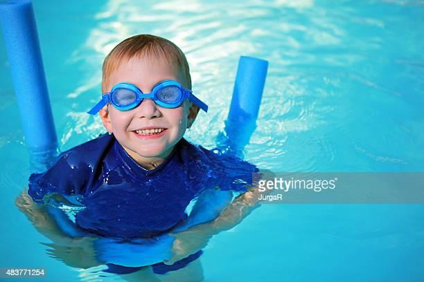 Kind mit Aquanudel und Schwimmbrille lernen, schwimmen