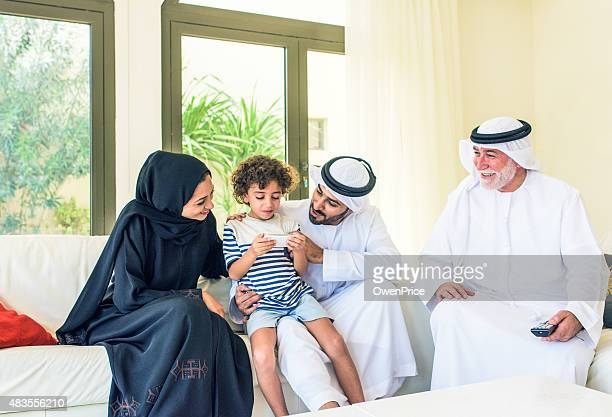 Child with parents playing game on smart phone