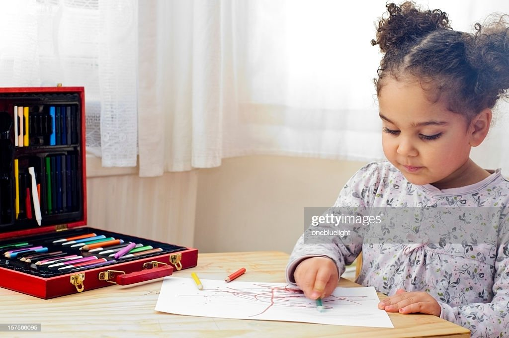 Child with pony tails drawing with colored crayons