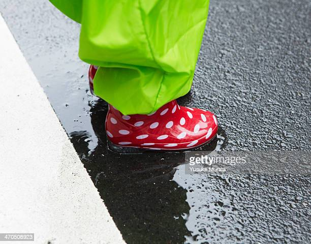 Child with rain boots standing in a puddle