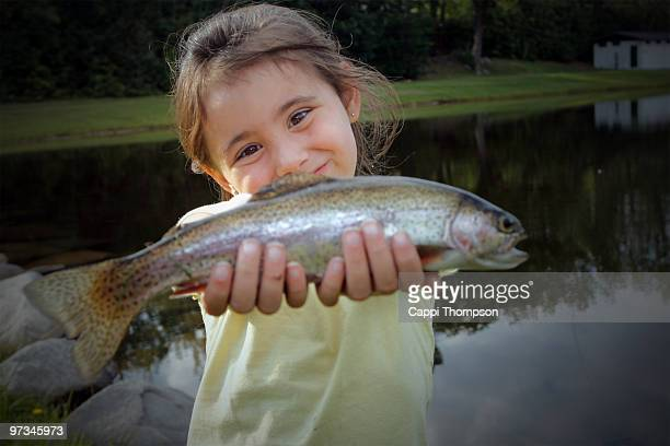 Child with rainbow trout.
