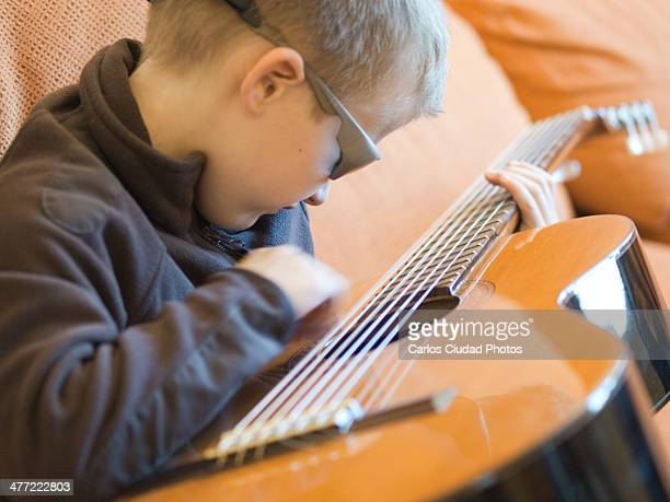 Child with sunglasses playing guitar