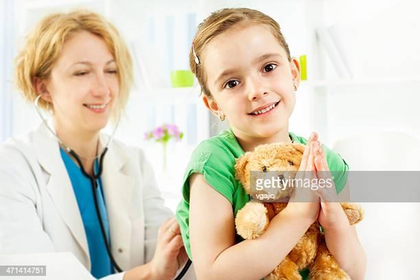 Kind mit Teddybär in Arzt-Büro.