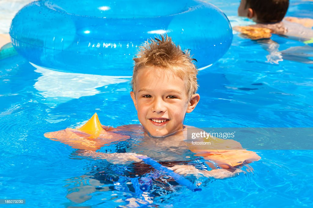 Swimming Pool Wings : Child with water wings relaxing the swimming pool stock