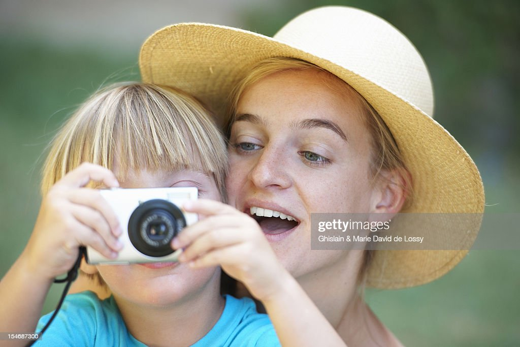 Child with woman taking a photograph : Stock Photo