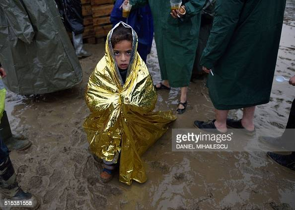 TOPSHOT A child wrapped in a survival blanket looks as migrants queue for hot soup on March 13 in a makeshift camp at the GreekMacedonian border near...